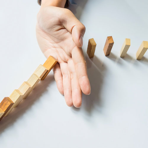 A hand stopping a row of dominoes from falling