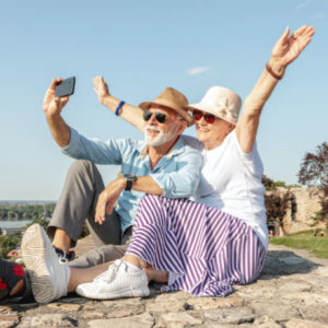 An elderly couple taking a selfie on holiday