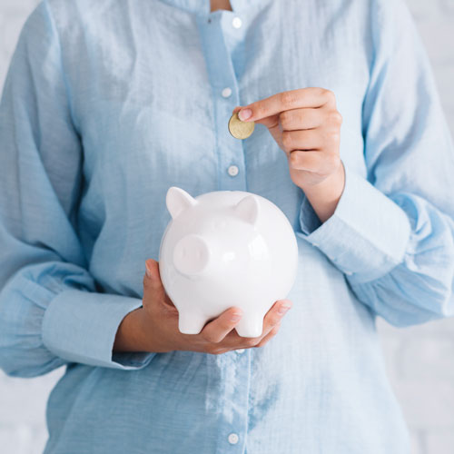 Someone with a blue shirt putting a coin into a white piggy bank
